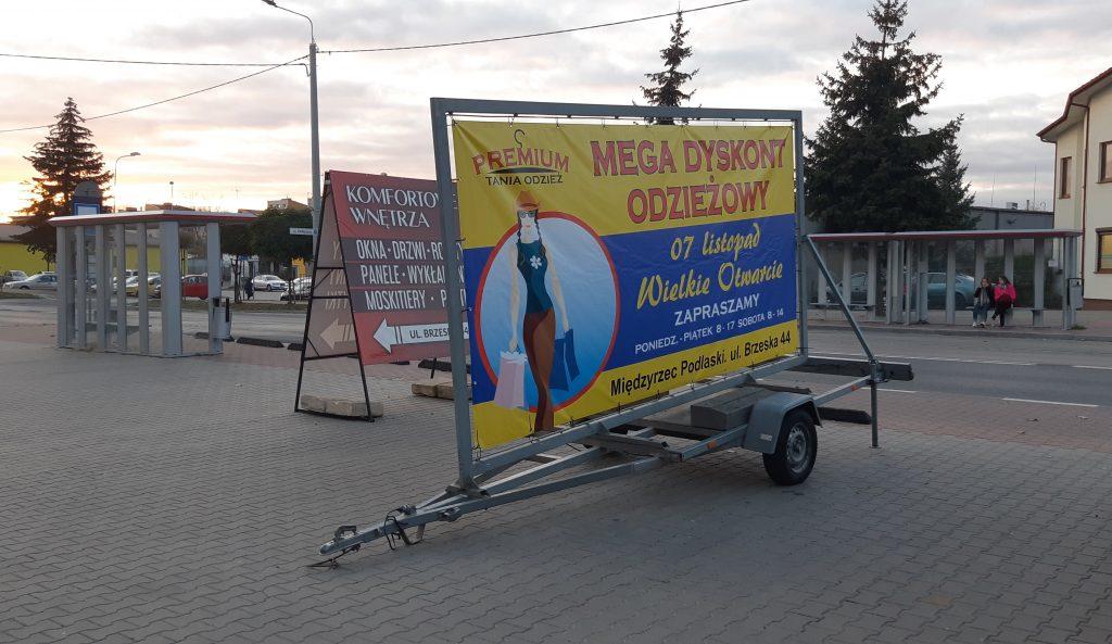 Reklama stacjonarna na przyczepce reklamowej.